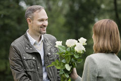 Man gives flowers woman Stock Images