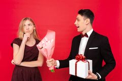 Elegant man, gives a gift and a bouquet of flowers, displeased girl, on a red background royalty free stock photos