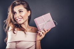 Happy beautiful woman with a gift box for Valentine's day on black background. Happy beautiful woman with a gift box for Valentine's day Royalty Free Stock Photos