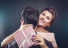 Man gives a gift box to his girlfriend for Valentines day. Stock Images