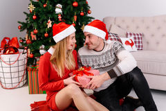 The man gives a gift girl near the Christmas tree Royalty Free Stock Photos