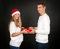 The man gives the gift pregnant girl in Santa hat Royalty Free Stock Images