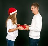 The man gives the gift pregnant girl in Santa hat Stock Photography