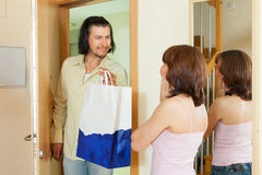 Man gives gift to woman at home royalty free stock photo