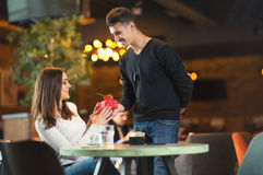 Man gives a gift to a young girl in the cafe Stock Photography