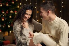 The man gives the girl an engagement ring, couple is in christmas lights and decoration, dressed in white, fir tree on dark wooden stock image