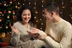 The man gives the girl an engagement ring, couple is in christmas lights and decoration, dressed in white, fir tree on dark wooden royalty free stock image