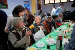 Man gives interview at the Christmas charity dinner for the poor people. KIEV, UKRAINE: Poor people have lunch at the Christmas charity dinner for the homeless royalty free stock photo