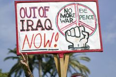 A man gives the peace sign and holds a sign saying, Out of Iraq Now at an anti-Iraq War protest march in Santa Barbara, California Stock Photo