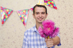 Man gives purple flowers. A man in a cardboard hood gives purple flowers on holiday stock photography