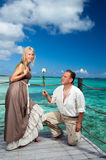 Man gives a rose to the woman on the turquoise sea Royalty Free Stock Photo