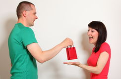 Man gives surprised woman gift for birthday Royalty Free Stock Images