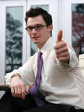 Man gives thumbs up. Attractive businessman gives the thumbs up signal (focus on model's face Stock Image