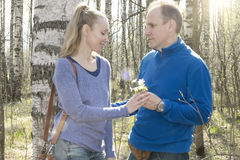 The man gives to the woman a bouquet of snowdrops in a birchwood in the spring Royalty Free Stock Images