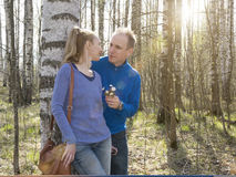 The man gives to the woman a bouquet of snowdrops in a birchwood in the spring Royalty Free Stock Photo