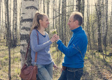 Man gives to the woman a bouquet of snowdrops in a birchwood in the spring, toning Stock Image