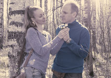 The man gives to the woman a bouquet of snowdrops in a birchwood in the spring, toning Royalty Free Stock Images