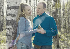 Man gives to the woman a bouquet of snowdrops in a birchwood in the spring, toning Stock Images