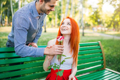 Man gives woman flower, romantic date Stock Photos