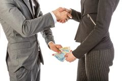 Man gives woman money while shaking hands Stock Photos
