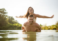 Man gives woman piggy ride on a summer day in the lake Stock Photography