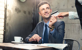 Man giving bank card to waiter Royalty Free Stock Photos