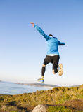 Man giving a big jump while practicing trail running Stock Photos