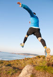 Man giving a big jump while practicing trail running outdoors Stock Image