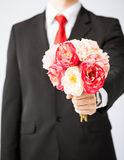 Man giving bouquet of flowers. Close up of young man giving bouquet of flowers Royalty Free Stock Photography