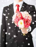 Man giving bouquet of flowers. Love, romance, holiday, celebration concept - young man giving bouquet of flowers Royalty Free Stock Image
