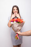 Man giving a bouquet of flowers and surprised woman isolated on white background Stock Photo