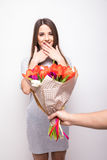 Man giving a bouquet of flowers and surprised woman isolated on white background Stock Images