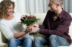 Man is giving a bouquet of flowers to woman Royalty Free Stock Photos