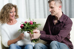 Man is giving a bouquet of flowers to woman Royalty Free Stock Images