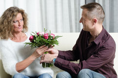 Man is giving a bouquet of flowers to woman - she is in doubt Stock Photos