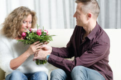 Man is giving a bouquet of flowers to woman - she is smelling th Stock Photo