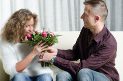 Man is giving a bouquet of flowers to woman - she is smelling th Royalty Free Stock Photography