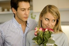 A man giving a bouquet of roses to a woman Stock Images