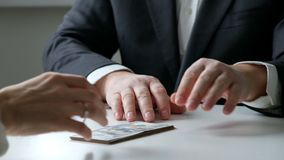 A man giving bribe money in a white envelope to another businessman in a corruption scam, close up. A man giving bribe money in a white envelope to another stock footage