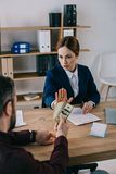 Man giving bribe to businesswoman at workplace. In office stock photos