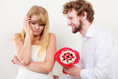 Man giving candy bunch flowers to sad woman. Royalty Free Stock Image