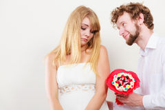 Man giving candy bunch flowers to sad woman. Royalty Free Stock Images