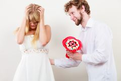 Man giving candy bunch flowers to sad woman. Handsome men giving pretty sad depressed women candy bunch bouquet flowers. Unhappy couple Royalty Free Stock Photography