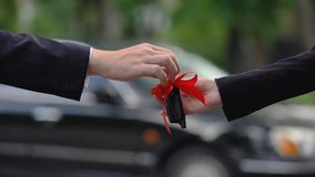 Man giving car key with big red bow to woman, amazing surprise, precious gift. Stock footage stock video footage