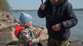 Man giving a caught fish to his granddaughter. Senior man giving freshly caught fish to his granddaughter. Grandfather and granddaughter are fishing in spring stock footage