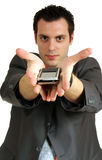 Man giving cellphone. A young businessman, holding a cellphone(mobile) on his spread palms with hands pointing forward Stock Image
