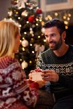 Man giving Christmas gift to happy young woman at home Stock Images