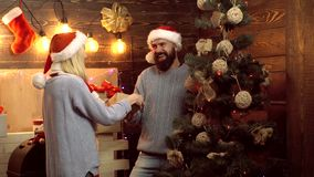 Man giving a Christmas present. Pretty girl surprising with a Christmas gift. New year funny couple. Home Christmas. Atmosphere. Open a New Years gift stock video footage