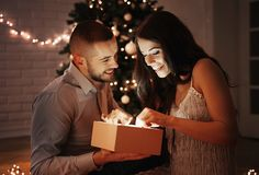 Man giving a Christmas present to his girlfriend. Christmas tree in the background royalty free stock image