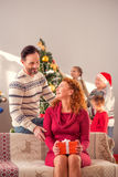 Man giving Christmas present to lady Stock Images